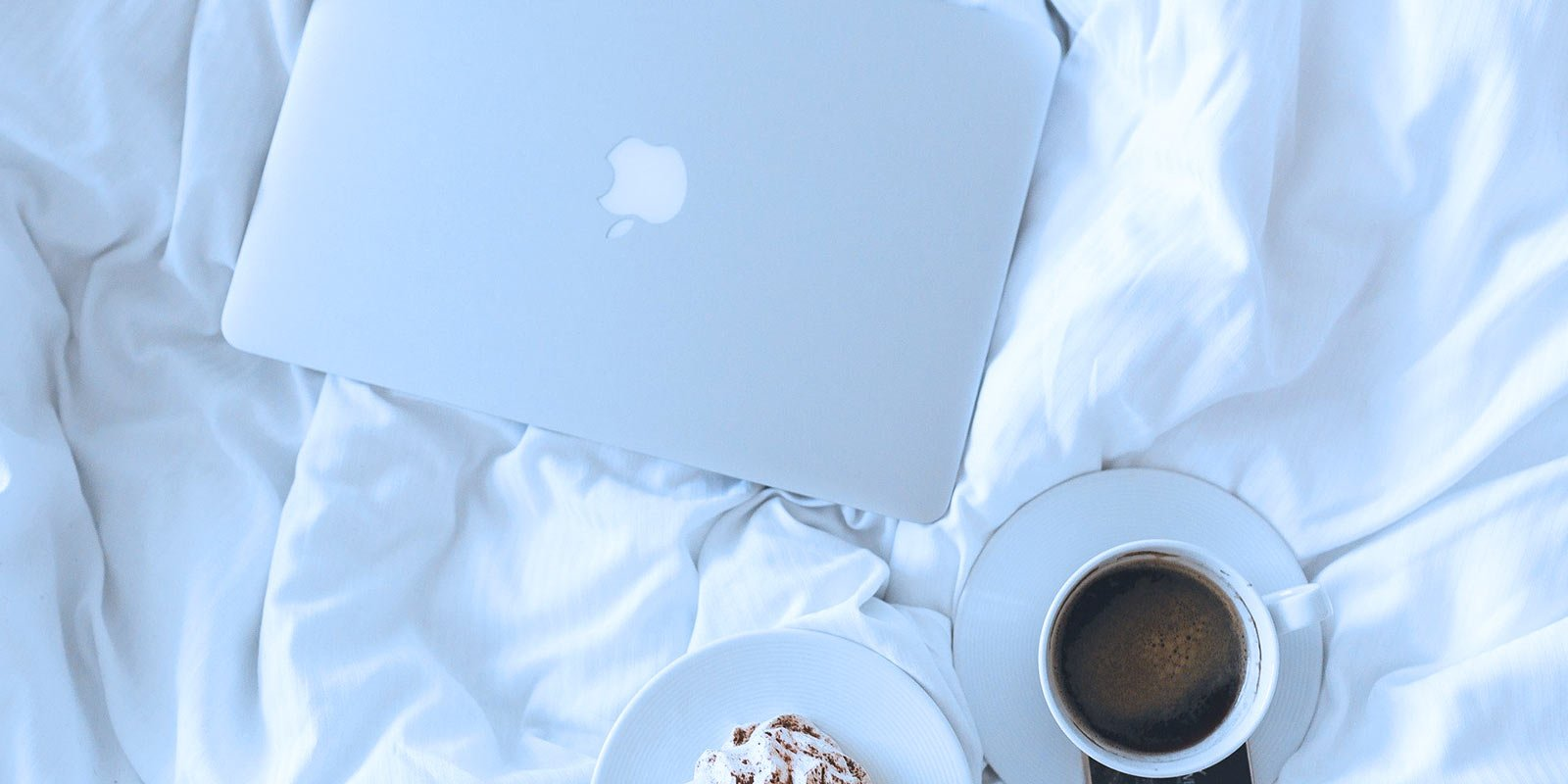 Comfy bed with laptop inviting Entrepreneur to get better sleep for peak performance.